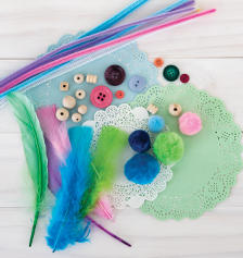 Art and craft supplies: feathers, buttons, straws and doilies.